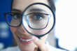 Woman with glasses looks through magnifying glass and smiles. Research and analysis of modern market startup startup concept