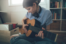 Young Woman Playing Guitar At ...