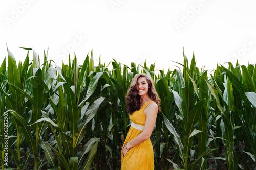 Photo portrait of young beautiful woman wearing a yellow dress standing in a green corn field