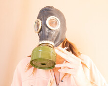 Woman Wearing Gas Mask Holding Cigarette Against Wall