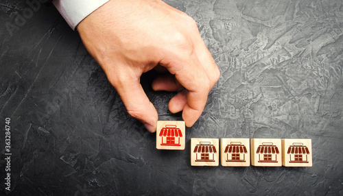 Man Adding a block with a store icon to others Fototapet
