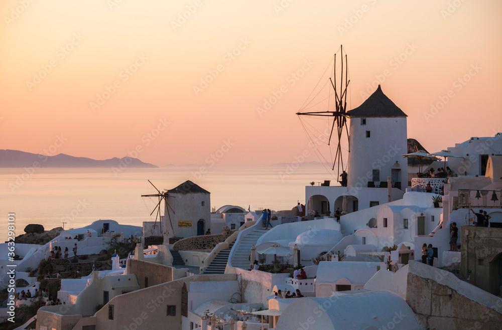 Fototapeta Oia town, on the Greek Santorini island (Thira). Tour of the sunset overlooking the mill