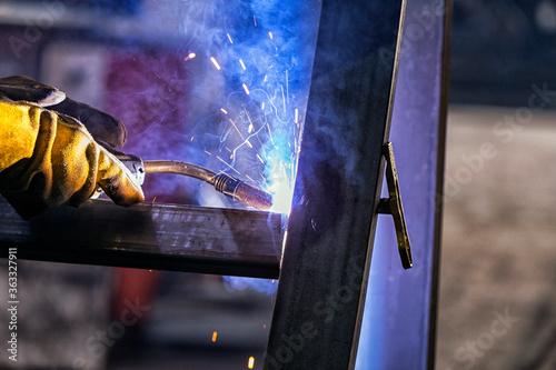 The welder is welding a structural steel with gas metal arc welding ( GMAW ) in the workshop Slika na platnu