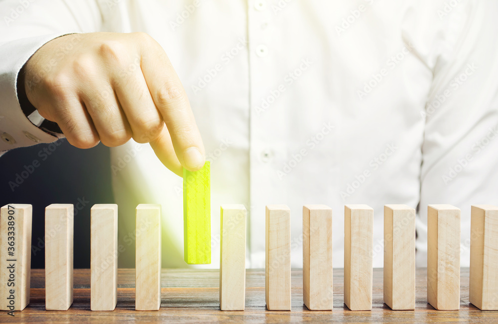 Fototapeta A man puts green dominoes in a row. Business management and processes. Correct errors, make improvements. Risk management, integration into upgrades to the system, implementation into legislation.