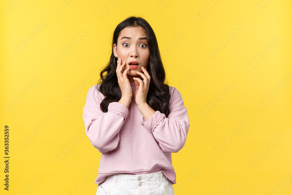 Fototapeta People emotions, lifestyle and fashion concept. Shocked and concerned insecure asian woman react to bad shocking news, gasping and touching face, stare anxious at camera, yellow background