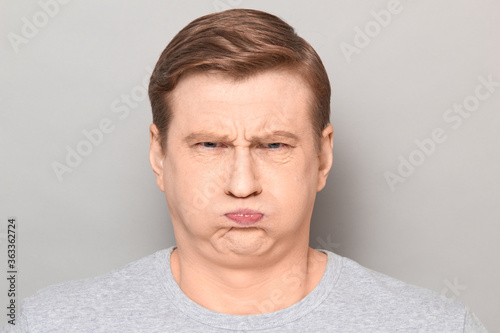 Portrait of funny goofy man puffing out his cheeks and pouting lips Fototapet