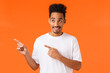canvas print picture - Amused and entertained handsome young african-american man in white t-shirt, curiously looking and pointing upper left corner, smiling pleased, found best shop with great discounts, orange background