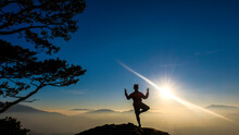 Silhouette Woman Doing Yoga On Mountain Peak Against Sky During Sunrise