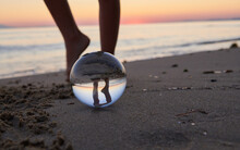Low Section Of Person Seen Through Crystal Ball At Beach