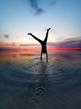 Handstand Of A Girl At Sunset In The Sea