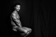 Naked Man Sitting Against Black Curtain