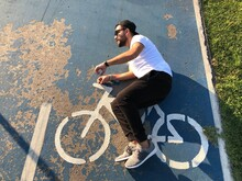 Optical Illusion Of Man Riding Bicycle On Sign At Road