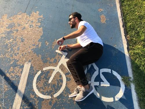 Fototapeta premium Złudzenie optyczne człowieka, jazda na rowerze na znak na drodze