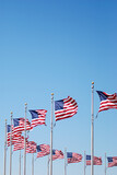 Low Angle View Of National Flags Against Clear Blue Sky