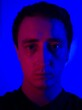 Leinwanddruck Bild - Close-up Portrait Of Young Man Against Blue Background