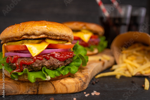 Fototapeta Hamburger on a black wooden background with french fries and soda closeup, fast food obraz