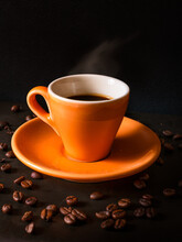Close-up Of Coffee Cup And Beans On Black Background