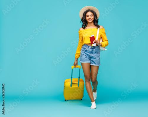 Obraz Ethnic tourist with luggage walking towards camera. - fototapety do salonu