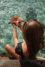 Starfish In Human Hand On Turquoise Tropical Beach. Shells And Starfish On The Sea. Summer Photo Woman Hold In Hands Starfish