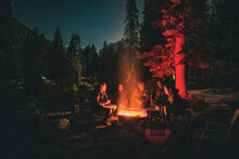 Men Sitting By Bonfire In Forest At Night