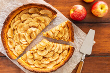 Homemade Baked French Apple Tart, An Open Faced Apple Pie, Aside Gala Apples And Silver Vintage Cake Server Or Tart Server On A Baking Paper Sheet On Vintage Wood Table. Flat Lay, Top View.