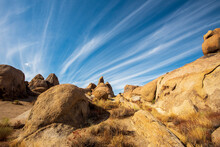 Desert Rock Formations With Streaky Clouds In Blue Sky