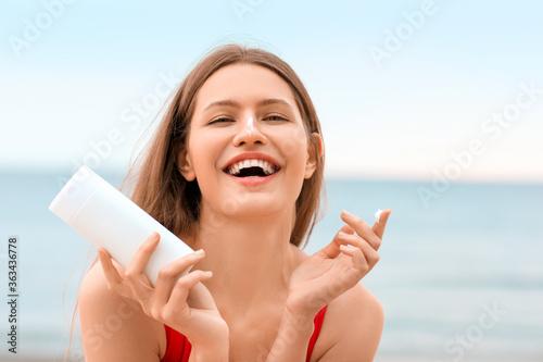Young woman applying sunscreen cream on sea beach