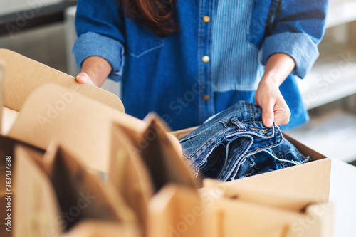 Tablou Canvas Closeup image of a woman receiving and opening a postal parcel box of clothing a