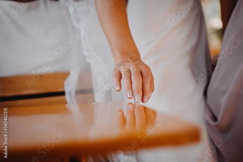 Fototapeta Hand der Braut mit Ehrering auf dem Tisch