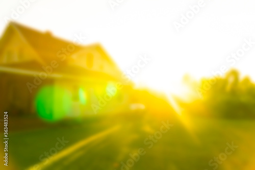 Fototapeta Blurred abstract background of Luxury house at the sunset. House exterior theme creative abstract blur background with bokeh effect. Blurred house and lawn obraz