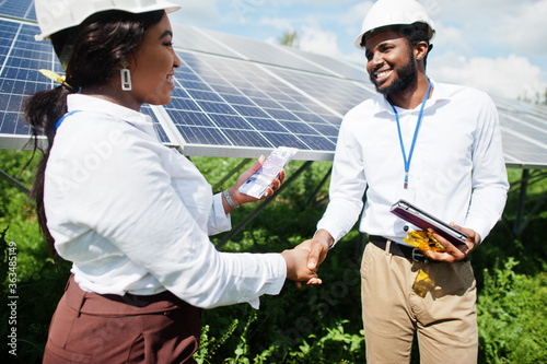 African american technician checks the maintenance of the solar panels. Group of three black engineers meeting at solar station and make a deal with money.