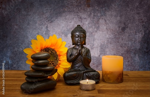 Fototapety, obrazy: Closeup of a small statue of Buddha on the table with stacked stones, candles and a flower