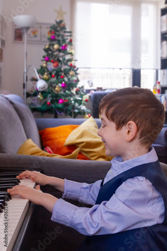 Cuadros en Lienzo Boy Sitting Playing Piano At Home At Christmas