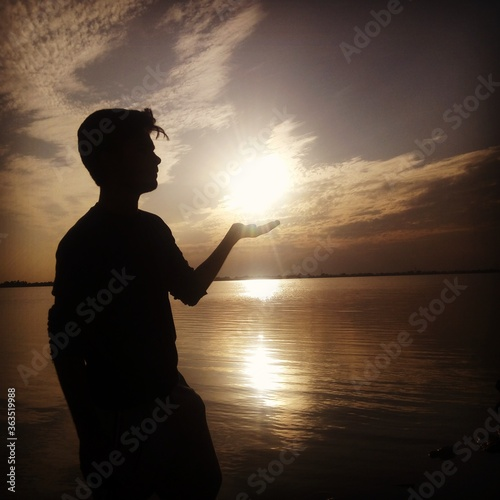 Fototapeta premium Optical Illusion Of Silhouette Man Holding Sun At Lakeshore During Sunset