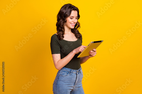 Profile side view portrait of her she nice attractive smart clever cheerful cheery wavy-haired girl holding in hands ebook studying web isolated on bright vivid shine vibrant yellow color background