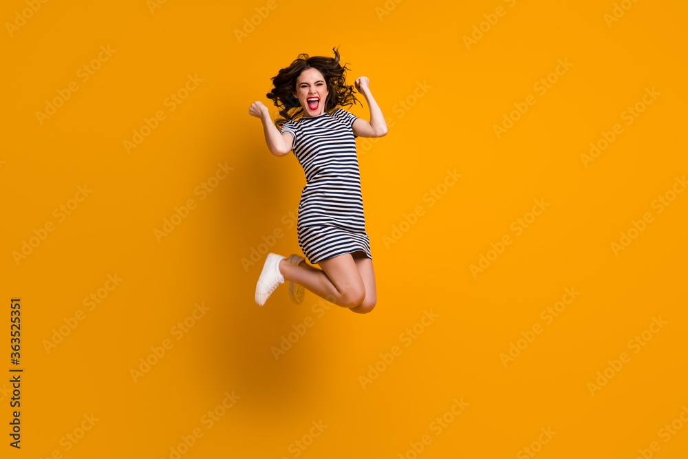 Fototapeta Full length photo of crazy curly lady jump high raise fists celebrate amazing victory sportive competitions wear white casual striped short dress shoes isolated yellow color background