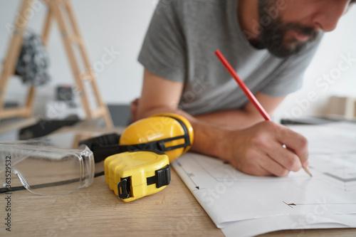 Fototapeta Carpenter making corrections to plans obraz