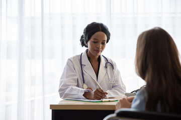 Doctor Writing Prescription While Patient Sitting At Hospital