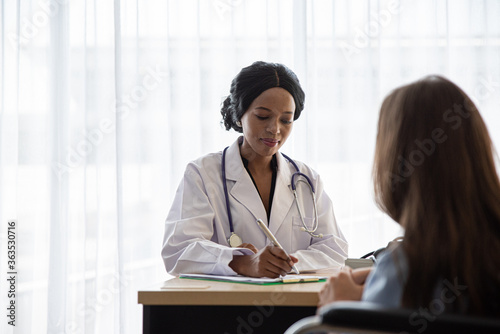 Photo Doctor Writing Prescription While Patient Sitting At Hospital