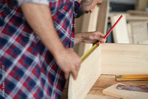 Fototapeta Back view of carpenter measuring wooden plank obraz
