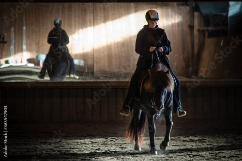 Vászonkép Woman Riding Horse Indoors