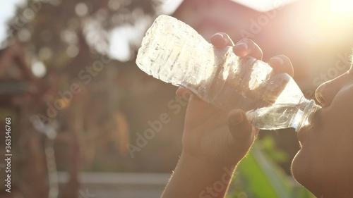 Fotografiet Boy Drinking Water Of Bottle Feel Very Thirstily In Hot Day Preventing Heat