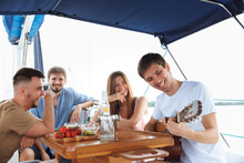 Group Of Happy Friends Drinking Vodka Cocktails At Boat Party Outdoor, Cheerful And Happy. Young People Playing Guitar In Sea Tour, Youth And Summer Vacation Concept. Alcohol, Vacation, Resting.