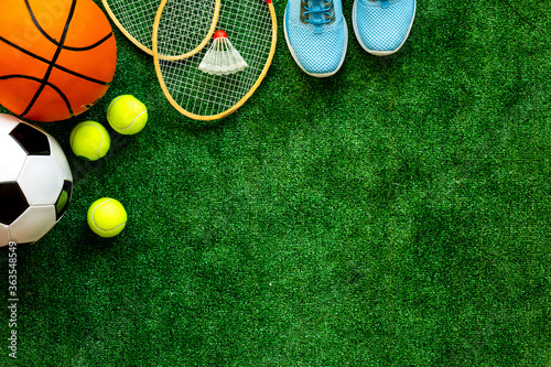 Obraz na plátne Sport games equipment - balls, sneakers, rockets - on grass top view copy space