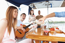 Group Of Happy Friends Drinking Vodka Cocktails At Boat Party Outdoor. Young People Playing Guitar In Sea Tour, Youth And Summer Vacation Concept. Alcohol, Vacation, Resting. Focus On Pouring Drink.