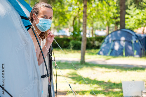 Fototapeta Woman wearing medical mask stepping out of camping tent. obraz