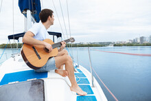 Young Cheerful Man Playing Guitar At Boat Party Outdoor, Smiling And Happy. Adventure In Sea Tour, Youth And Summer Vacation Concept. Alcohol, Vacation, Resting, Music Concept. Good Vibes And Emotions