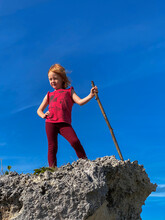 Low Angle View Of Girl Standing On Rock Against Blue Sky