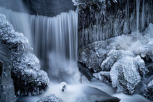 Detail Of A Frozen Small Waterfall In A Forest Creek With Icicles