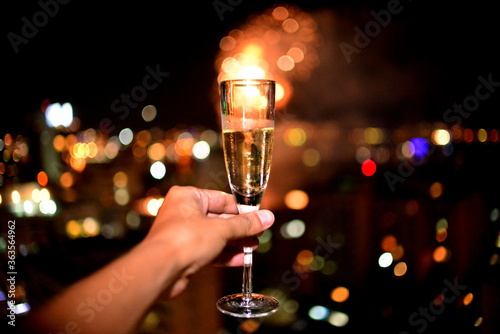 Papel de parede Close-up Of Hand Holding Champagne Glass Against Fireworks